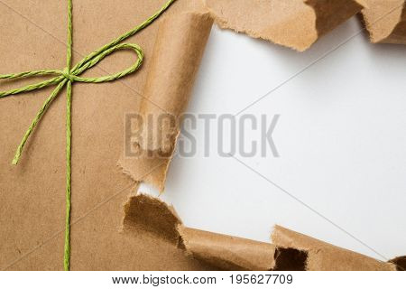 Package with bow ripped on white background