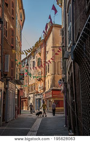 Draguignan, France - July 11, 2016. View of alley with townhouses and pedestrians in the city center of the lively and gracious town of Draguignan. Var department, Provence region, southeastern France