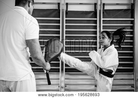 Tae kwon do instructor with girl on training indoors black and white image