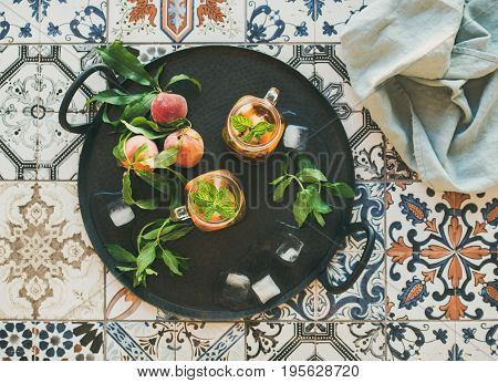 Summer refreshing cold peach ice tea with fresh mint in glass jars on metal tray over colorful oriental ceramic tile background, top view, flat lay