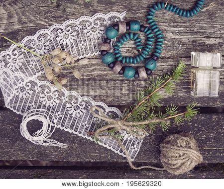 stillife with decorative materials ribbons and threads on a wooden background