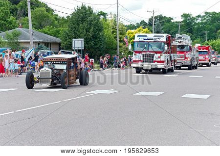 MENDOTA, MN/USA - JULY 8, 2017: Custom car and firetrucks in motorcade lineup down main street of historic city for Mendota Days Parade. Mendota is one of the first permanent settlements in Minnesota.