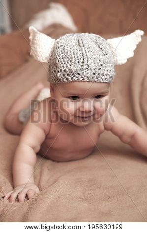 Cute Baby Boy Lie On A Beige Background Wearing A Crochet