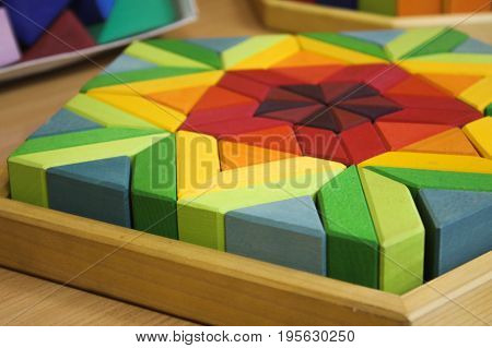 The colored wooden cubes for children on the table. The colored blocks of wood on the table. Abstract objects, mosaic, puzzle for the development of mental abilities, logical thinking. Board games for children in game room, playroom