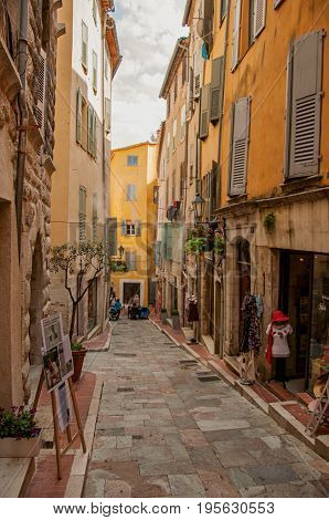 Grasse, France - July 12, 2016. View of narrow street and buildings with shops in Grasse, a friendly town known for producing perfumes. Alpes-Maritimes department, Provence region, southeastern France