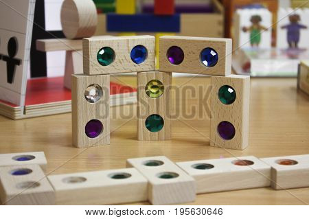 The colored wooden cubes for children on the table. The colored blocks of wood on the table. Abstract objects, mosaic, puzzle for the development of mental abilities, logical thinking. Board games for children