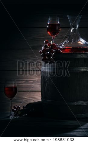 Barrel, decanter and glasses with red wine in a dark cellar. Still life on a theme of red wine. Magical light.