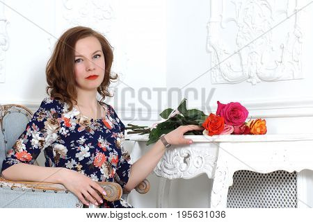 Beautiful young girl in bright colorful dress sits in a chair near a white dressing table in the room and looks at the camera