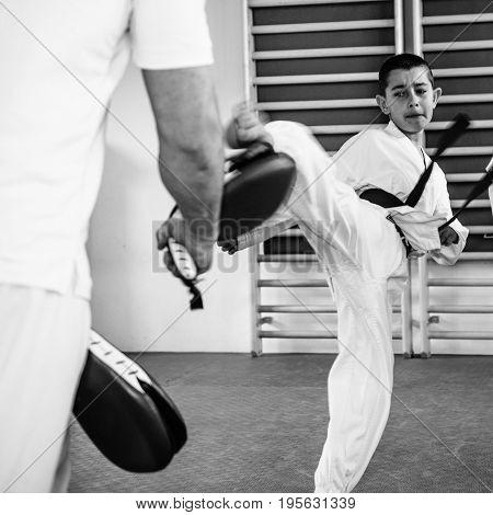 Taekwondo training for kids on training indoors black and white image