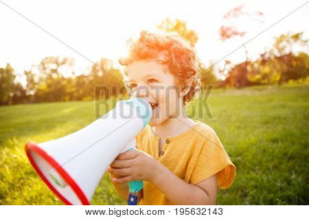 Wavy haired blonde boy wearing orange shirt standing in field speaking in megaphone.