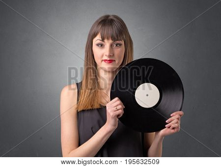 Young lady holding vinyl record on a grey background