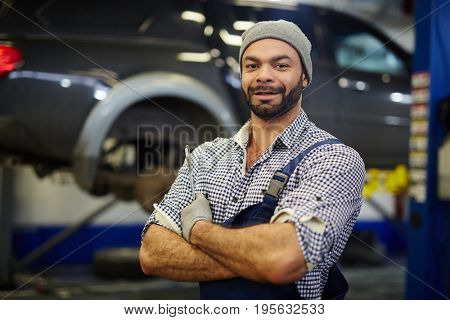 Motor mechanic with wrench in car service workshop