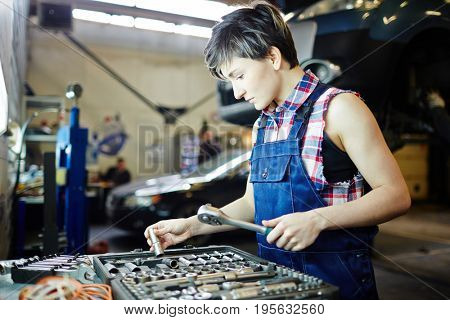Woman mechanic choosing spare-parts in the kit