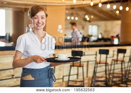 Hospitable waitress holding tray with cup of coffee
