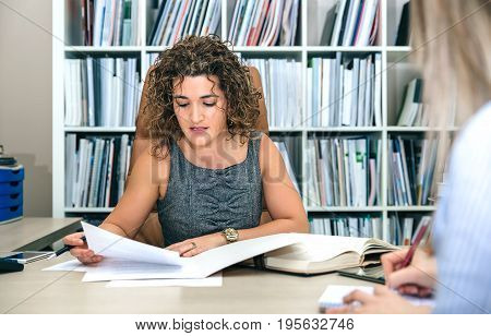 Portrait of curly businesswoman working with documents in office while blonde secretary taking notes