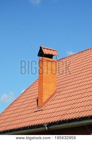 Red Metal Roof Tiles with brick chimney. Roofing Construction roof repair.