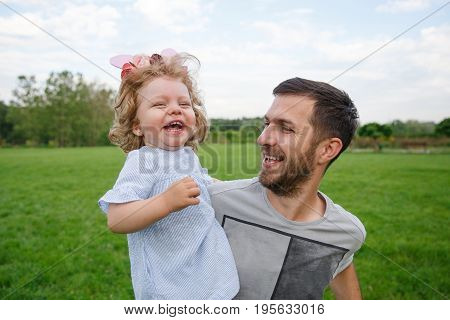Happy brunette father carrying blonde smiling daughter with bow in park.