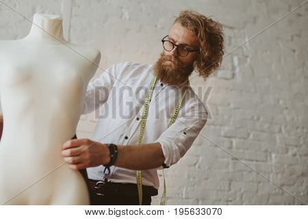 Blonde bearded male dressmaker wearing white shirt tape measure fitting cloth on mock-up standing against white brickwall.