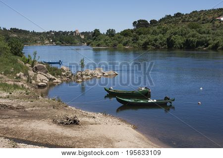 View of traditional wooden boats in the Tagus river with Almourol castle as background