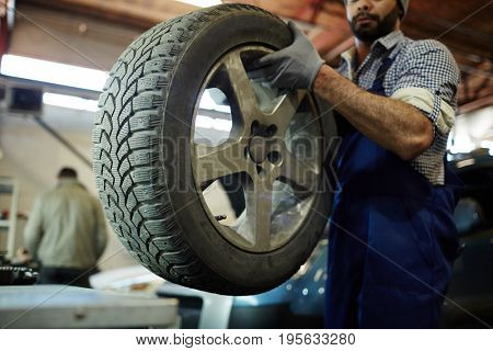 Worker of car technical service holding tire to change