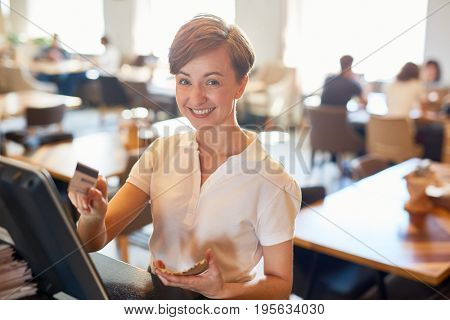Successful staff of coffee-shop entering order of client in computer