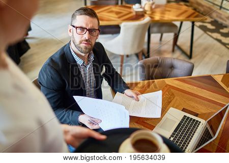 Businessman with papers looking at servant in cafe