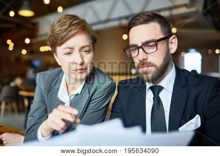 Two economists discussing papers or contract