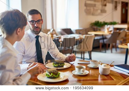 Business leaders having meals in cafeteria or restaurant