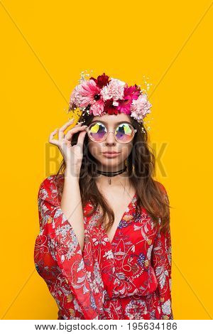Hipster brunette woman wearing red dress with ornament flower chaplet touching glasses.