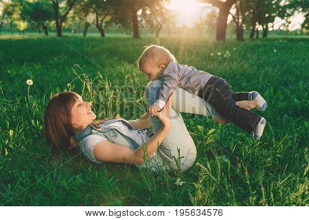 happy mother and son at sunset sunlight. happy family on nature. mom and baby lying are playing and laughing in the green grass