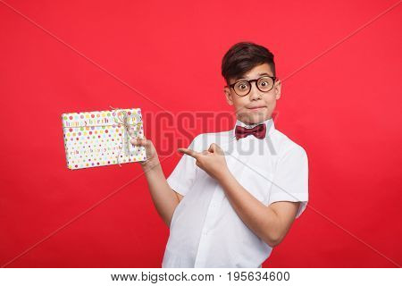 Little boy in glasses holding present and pointing at it on red background.