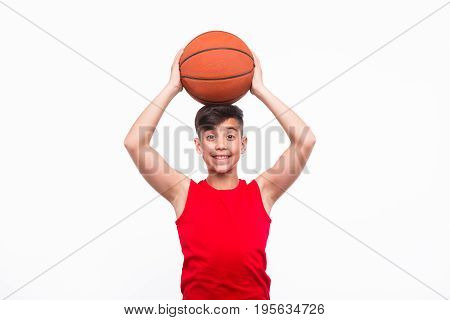 Content boy in sportswear holding basketball on head and smiling at camera on white.