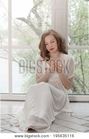 A beautiful girl in a white dress is sitting on the floor with her back to the window. White light surrounds the woman. She took off her shoes and looked at the present pearl necklace.