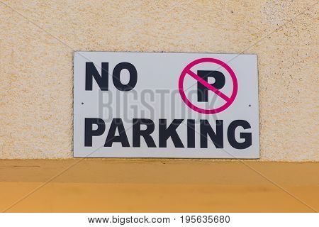 No parking sign. Nameplate on the wall