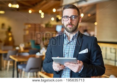 Confident ceo with touchpad networking in cafe