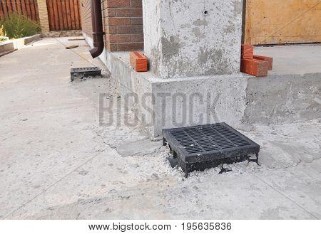 Rain gutter downspout drainage installation. Gutter Downspout for Better Home Drainage and Foundation Wall Waterproofing.