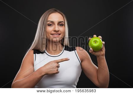 Sporty beefy blonde woman smiling wearing top pointing at green apple she holds.