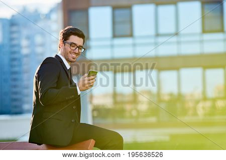Young broker texting in smartphone outdoors