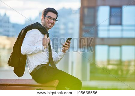 Happy employer with smartphone in urban environment