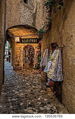 Saint-Paul-de-Vence, France - July 13, 2016. View of narrow alley with shop in Saint-Paul-de-Vence, stunning medieval town completely preserved. Provence region, southeastern France. Retouched photo