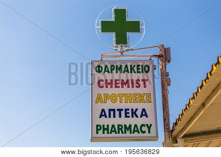 Pharmacy sign on the outside of a building. Pharmacy sign in different languages