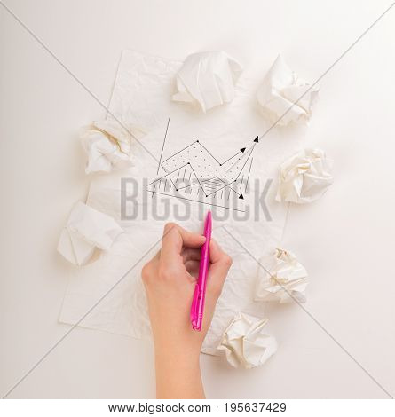 Female hand next to a few crumpled paper balls drawing a progress chart