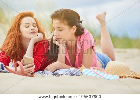 Two young women laying  sunbathing on a white sand beach, relaxing and sharing a smart phone with headphones, smiling outdoors. Tourists and technology lifestyle