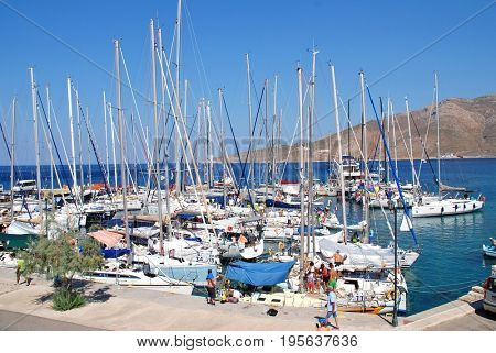 TILOS, GREECE - JULY 19, 2016: Yachts taking part in the annual Rhodes Cup yacht race moored in Livadia harbour on the Greek island of Tilos. The event is in its twentieth year.