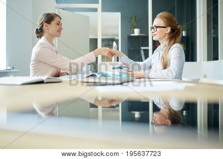 Businesswomen shaking hands over workplace after agreement or interview