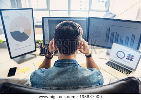 I have headache. Employee demonstrating weariness while having job on computer in apartment. He is looking at graphics on monitor with concentration
