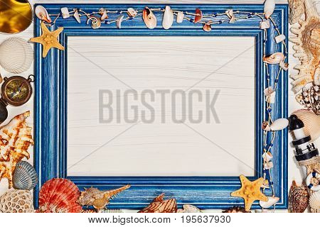 Mediterranean concept with blank rough painted frame and sea shells star fish and vintage metal compass
