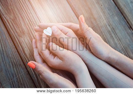 Mother and son holding white heart on wooden background