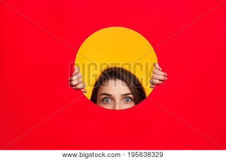 Crop woman looking out of circle cut in red paper on yellow background.