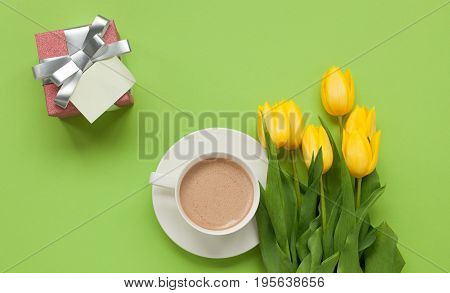 From above shot of yellow tulips on green table with cup of coffee and small giftbox.